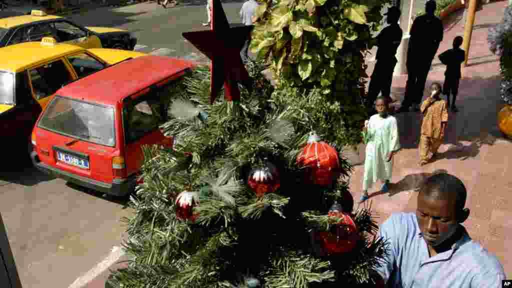 Ousmane Dembélé décore un des nombreux arbres de Noël mis en place à l'extérieur de la pharmacie où il travaille près des qui enfants mangent de la crème glacée dans le centre de Dakar, au Sénégal, 16 décembre 2005.