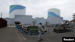 FILE - An employee of Kyushu Electric Power Co. walks in front of reactor buildings at the company's Sendai nuclear power plant in Satsumasendai, Kagoshima prefecture.