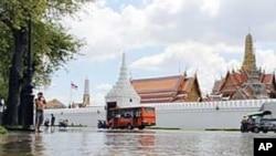 這名女童星期五在曼谷的大皇宮前面的洪水中