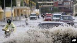 A Cambodian motorcyclist maneuvers through a flooded street along side cars on a rainy day in Phnom Penh.