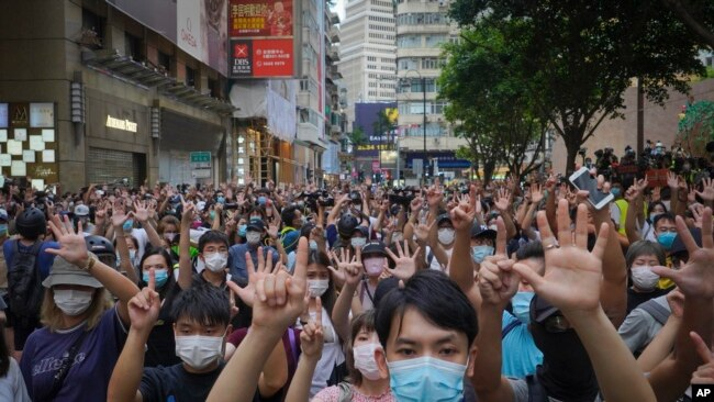 """Protesters against the new national security law gesture with five fingers, signifying the """"Five demands - not one less"""" on the anniversary of Hong Kong's handover to China from Britain in Hong Kong, Wednesday, July. 1, 2020. (AP Photo/Vincent Yu)"""