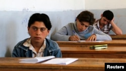 FILE - Students sit for their exam in what activists say is the only school in Hama not controlled by the Syrian regime, located in an area controlled by the Free Syrian Army, in Hama countryside, May 10, 2014.