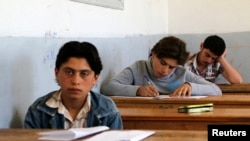 FILE - Students are seen taking exams in Hama, Syria, May 10, 2014.