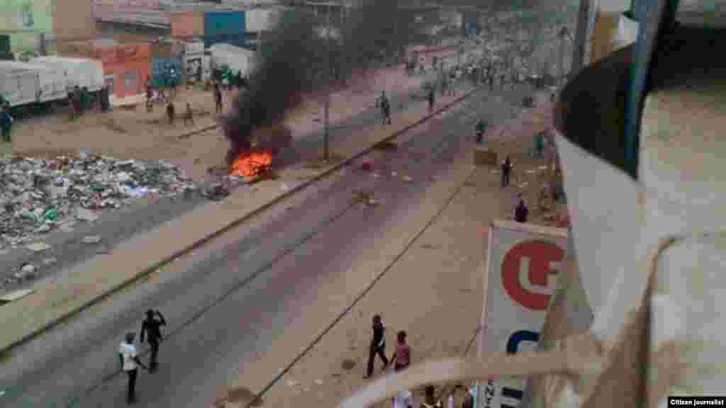 Quelques personnes marchent à pied à côté d'objets en flammes sur les rues de Luanda,, 5 octobre 2015. Photo deKolly Antonio Mwanza.