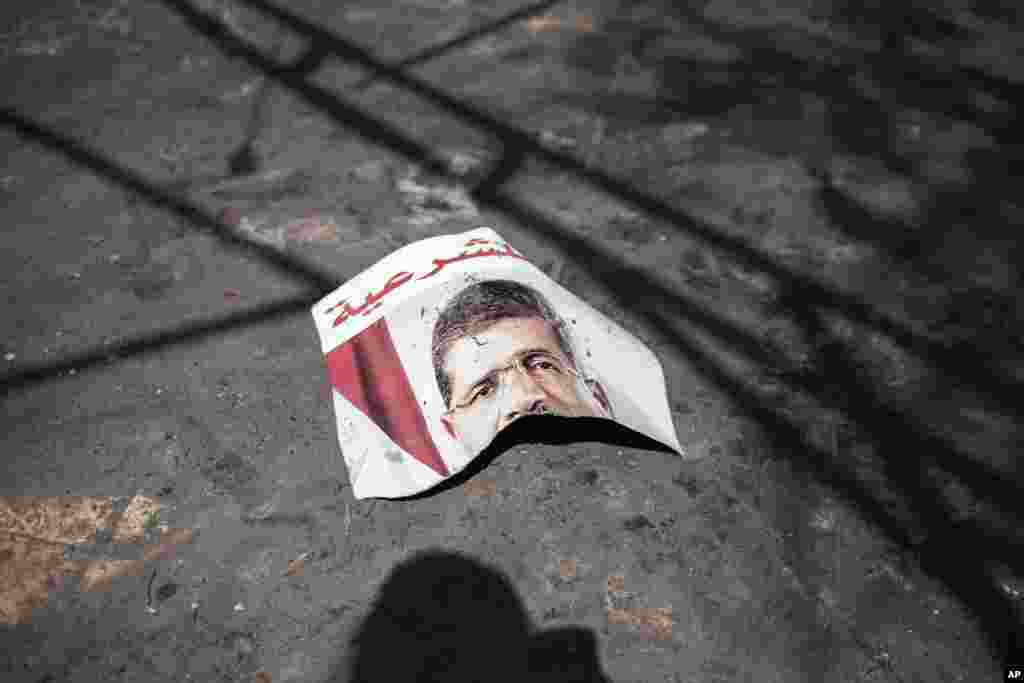 A ripped poster of Egypt's ousted President Mohamed Morsi lies on the ground in the courtyard of the Rabaah Al-Adawiya mosque in Nasr city, Cairo, August 21, 2013.