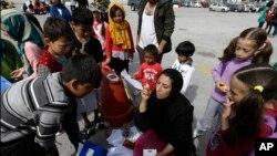 Ziaee Shole, au centre, un professeur d'université, parle aux enfants afghans au port d'Athènes du Pirée, 1er avril 2016.