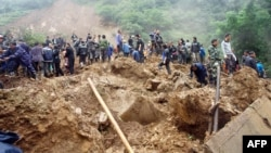 Rescuers search for victims after a landslide, triggered by sustained rains, buried a school and three farmhouses in Yiliang, southwest China's Yunnan province, October 4, 2012.