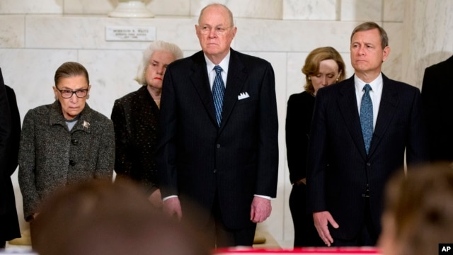 From left, Supreme Court Justices Ruth Bader Ginsburg and Anthony Kennedy, and Chief Justice John Roberts attend a private ceremony in the Great Hall of the Supreme Court in Washington for late Justice Antonin Scalia, Feb. 19, 2016.
