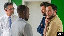 Wartawan harian Le Monde warga Perancis, Jean Philippe Remy (kedua dari kanan) dan juru foto Inggris Phil Moore (kanan), berbicara dengan Dubes Perancis untuk Burundi Gerrit van Rossum (kiri) dan diplomat Inggris di Burundi, Fleury Nyomana di Bujumbura pasca pembebasannya Jumat (29/1).