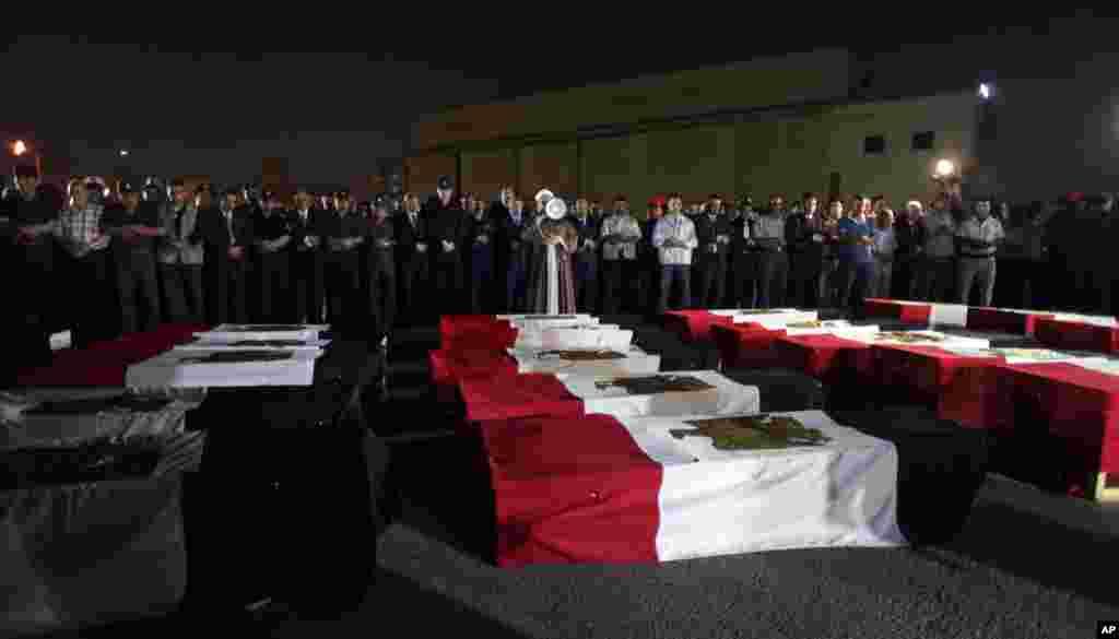 Pogrebna molitva nad zastavama prekrivenim lijesovima policajaca ubijenih pokraj Rafe, na Sinaju, izloženim na vojnom aerodromu Almaza, u Kairu, 20.8.2013.