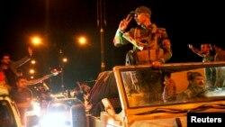 Warga melambaikan tangan pada para pejuang Kurdi yang menuju kota Kobani di Suriah dari provinsi Dohuk (28/10).