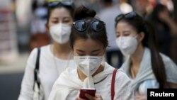 Turis memakai masker untuk mencegah tertular penyakit MERS di Seoul, Korea Selatan (10/6).