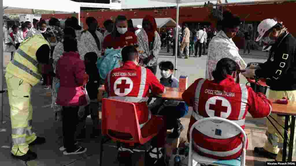 Des migratns érythréens reçoivent des premiers soins auprès de la Croix Rouge et des personnels de santé à Messine, Sicile, 6 ocotbre 2015 (Nicolas Pinault/VOA).