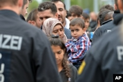 FILE - German policemen register refugees at the rail station in Freilassing, Germany, Sept. 14, 2015.