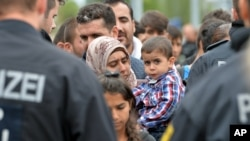 German policemen register refugees at the rail station in Freilassing, Germany, Monday, Sept. 14, 2015.