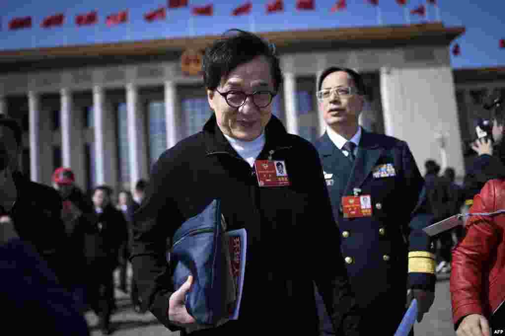 """2018年3月15日,香港演员成龙在中国人民政治协商会议闭幕式后离开北京人民大会堂。3月8日,文艺界第26组的成龙等38位全国政协委员递交了关于""""制定保护国格与民族尊严专门法""""的提案,被外界称作""""惩罚中国人的败类""""提案。推特上有些人为此嘲讽成龙。"""