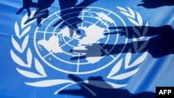 """Grb Ujedinjenih nacija i dečje ruke koje pokazuju """"V"""" znak pobede (Foto: AFP/HAZEM BADER)"""