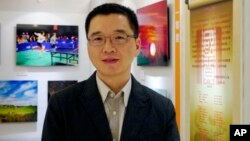 Yu Qiyi poses for a photo at an exhibition held at a hotel in Beijing. Yu had a promising career in a government investment company when he disappeared on his way home from a business trip March 1, 2013, photo taken Sept. 2, 2012.