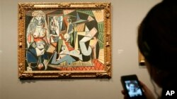"Visitor uses digital guide to ""Women of Algiers (Version O),"" 1955, by Pablo Picasso at The National Gallery, London, Feb. 24, 2009."