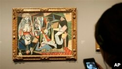"""Visitor uses digital guide to """"Women of Algiers (Version O),"""" 1955, by Pablo Picasso at The National Gallery, London, Feb. 24, 2009."""