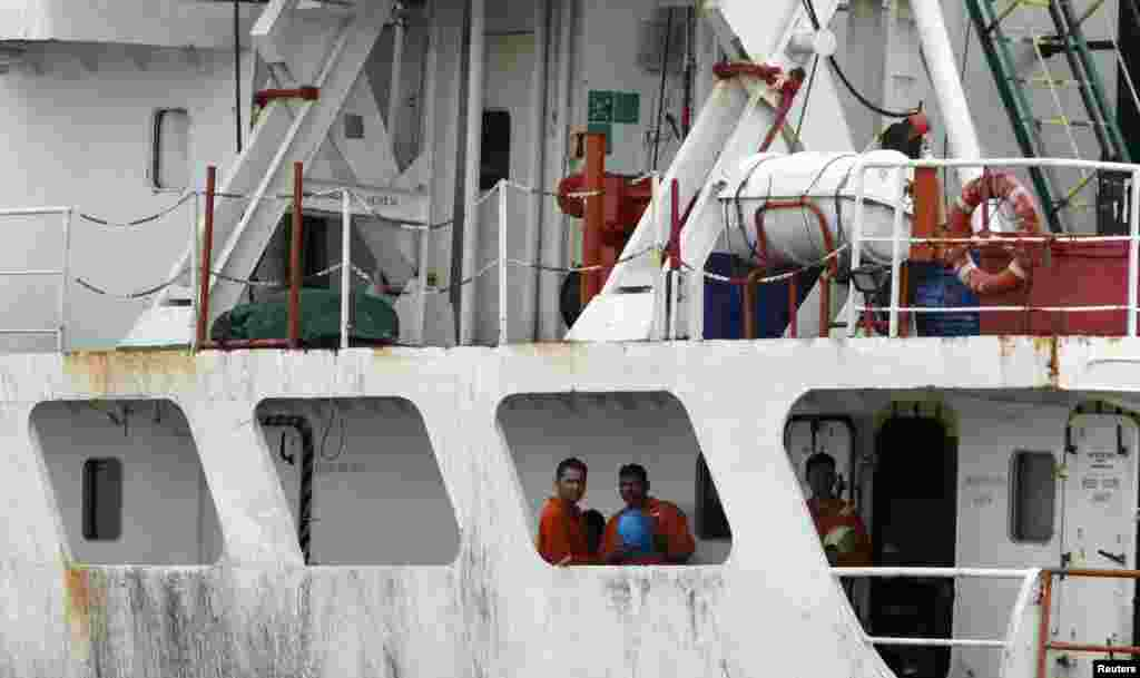 Crew members of the Panama-flagged cargo ship MV Asphalt Venture freed by pirates look out from the ship at the Kenyan Port of Mombasa, April 28, 2011.