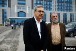FILE - Turkish authors Orhan Pamuk, left, and Murat Belge leave Kartal Justice Palace after Belge appeared in court on charges of insulting Turkish President Tayyip Erdogan in Istanbul, May 3, 2016.