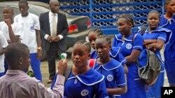 利比里亚教师给高中生量体温,防范埃博拉