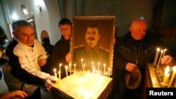 Arhiva - Ljudi pale sveće u crkvi tokom okupljanja u povodom godišnjice smrti sovjetskog lidera Josifa Staljina u njegovom rodnom gradu Gori, Gruzija, 5. marta 2017.