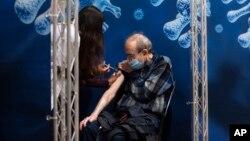 Seorang pria lansia menerima vaksinasi Covid-19 dari petugas medis di Ramat Gan, Israel (3/1).