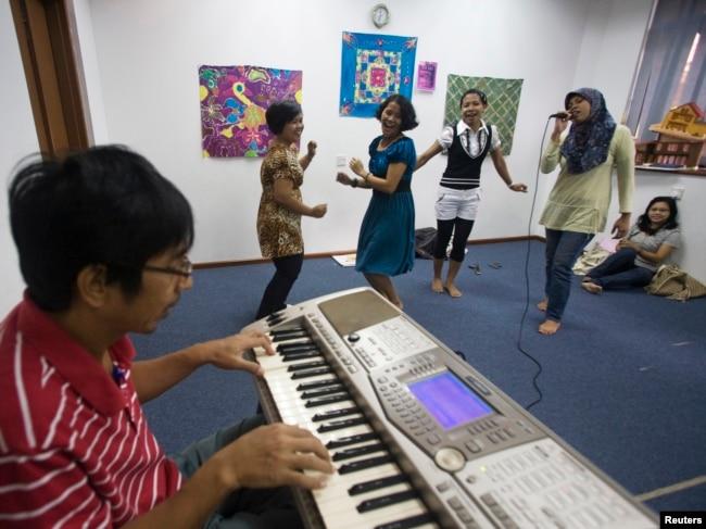 Sejumlah tenaga kerja wanita (TKW) asal Indonesia sedang berlatih menyanyi di Sekolah Indonesia Singapura saat hari libur, 12 Desember 2020. (Foto: Reuters)