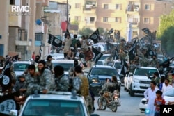 FILE - Fighters from the Islamic State parade through Raqqa, north Syria, in this undated file image posted June 30, 2014, by the Raqqa Media Center of the Islamic State group. Due to the decline in areas under the terror group's control and plunging revenues, IS reportedly is struggling to pay its foreign fighters' wages.