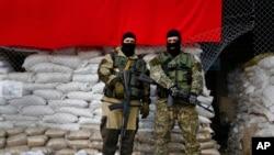 Pria bersenjata pro-Rusia menjaga barikade di depan balai kota Slovyansk, di Ukraina Timur (21/4). (AP/Sergei Grits)
