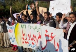 "FILE _ Pakistani students shout slogans against the Islamic State group holding a banner that reads ""down with Islamic State rally,"" in Islamabad, Nov. 20, 2014."
