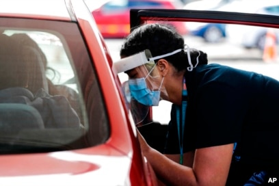 A health worker administers vaccinations at a pop-up drive-in clinic, in Auckland, New Zealand, Oct. 11, 2021.