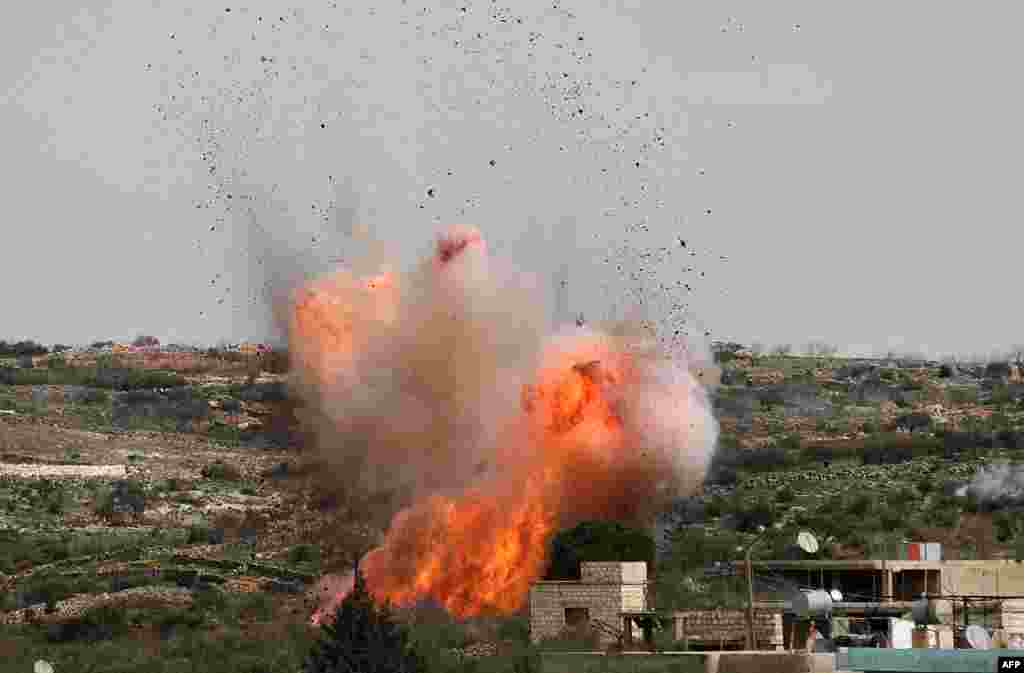 An explosion is seen following Russian airstrikes on the village of al-Bara in the southern part of Syria's northwestern Idlib province.