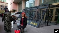 2014年5月1日,一位维吾尔妇女坐在乌鲁木齐街头,身后是铁笼保护下的中国武警。