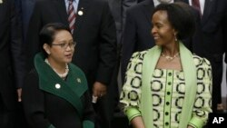 Indonesian Foreign Minister Retno Marsudi, left, talks with her South African counterpart Maite Nkoana-Mashabane as they prepare for a group photo prior to the opening session of the Asian African Ministerial Meeting in Jakarta, Indonesia, April 20, 2015.
