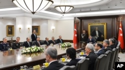 In this photo released by the Turkish Presidency Press Office, Turkish President Abdullah Gul (C) and Prime Minister Recep Tayyip Erdogan (7th L) during a meeting of the National Security Council in Ankara, Dec. 26, 2013.