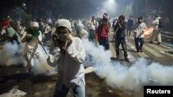 Người biểu tình thuộc phe Hồi giáo cứng rắn che mặt để tránh hơi cay của cảnh sát trong một cuộc biểu tình chống lại đô trưởng đương nhiệm Basuki Tjahaja Purnama của Jakarta, ngày 04 tháng 11 năm 2016.