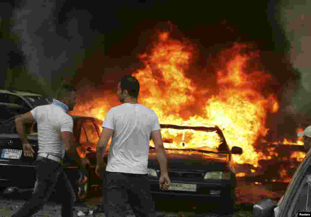 Men are seen near burning cars at the site of an explosion in Beirut's southern suburbs, July 9, 2013.