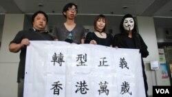3名闖解放軍營被告(左起)張漢賢、招顯聰、謝詠雯與另一名示威者,在裁判官宣判之後,在法庭外展示示威橫額及高呼港獨口號