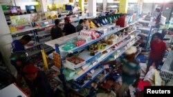 Nạn nhân sóng thần lục lọi một cửa hàng ở Palu sau thảm họa.