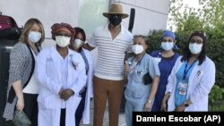 This image released by Damien Escobar shows Escobar with medical staff at Queens Hospital in the Queens borough of New York.