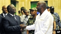 Ivorian President Laurent Gbagbo (R) speaks with Ivorian Defense minister Amani N'guessan (L) at presidential palace in Abidjan, 30 Nov 2009