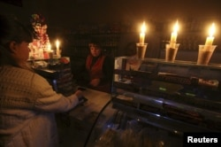 FILE - A customer visits a grocery lit with candles Nov. 22, 2015, due to a power cut, in Simferopol, Crimea.