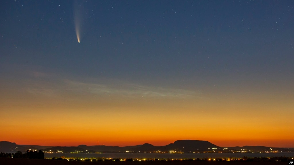 The Comet Neowise or C/2020 F3 is seen before sunrise over Balatonmariafurdo, Hungary, Tuesday, July 14, 2020. It passed closest to the Sun on July 3, and its closest approach to Earth will occur on July 23. (Gyorgy Varga/MTI via AP)