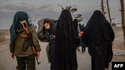 زنان نقابپوش که گزارش شده اعضا و یا همسران اعضای داعش هستند، تحت نظارت یک عضو نیروهای دموکراتیک سوریه