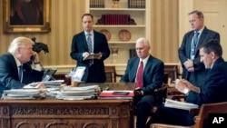 美國總統川普和俄羅斯總統普京通電話,旁觀者從左到有:白宮辦公廳主任普里巴斯,副總統彭斯,白宮發言人斯派塞與總統前國家安全事務助理弗林(2017年1月28日)