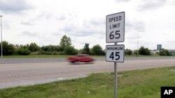 Un vehículo pasa una señal de límite de velocidad a lo largo de la Interestatal 64, en O'Fallon, Illinois.