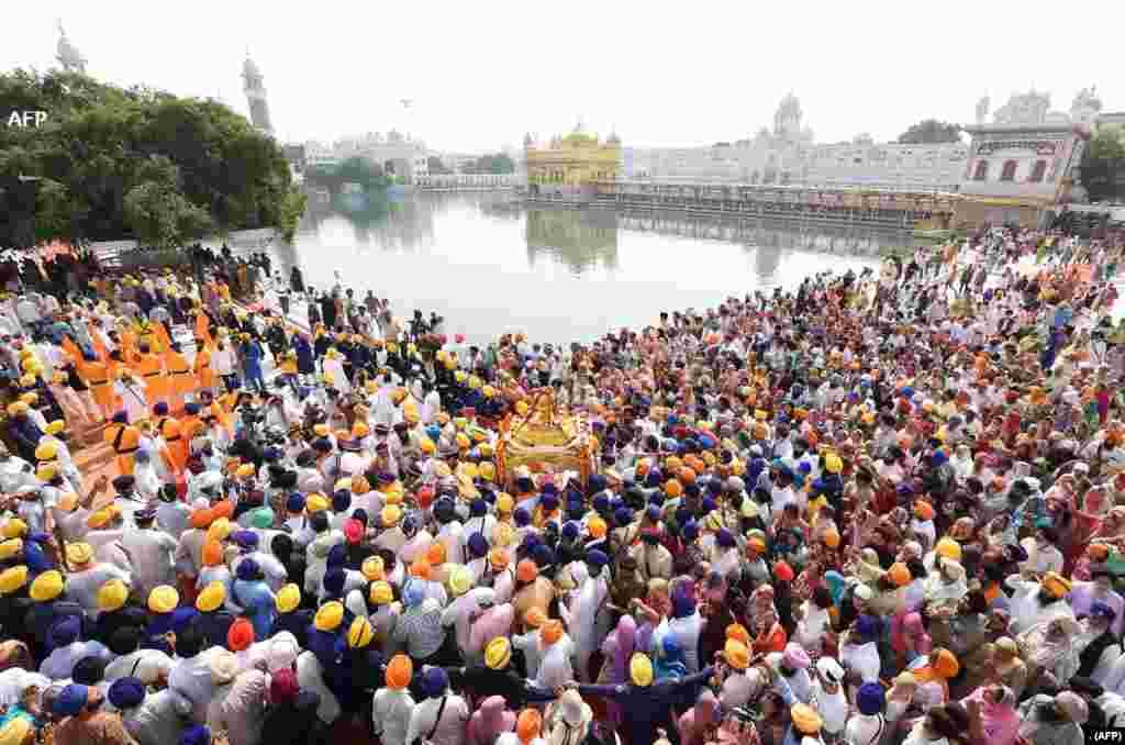 بھارت کے شہر امرتسر میں سکھوں کے مذہبی مقام 'گولڈن ٹیمپل' پر سکھ یاتری اپنی مقدس کتاب 'گرو گرنتھ صاحب' کو جلوس کی صورت میں لے جا رہے ہیں۔ یہ تہوار امرتسر کے بانی اور چوتھے سکھ گرو رام داس کے یوم ولادت پر منایا جاتا ہے